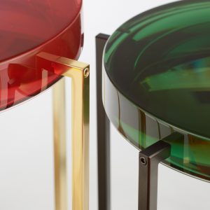 Resin Lens table close up in bottle green and rose with black and brass legs. Showing mirror reflections from internal dome