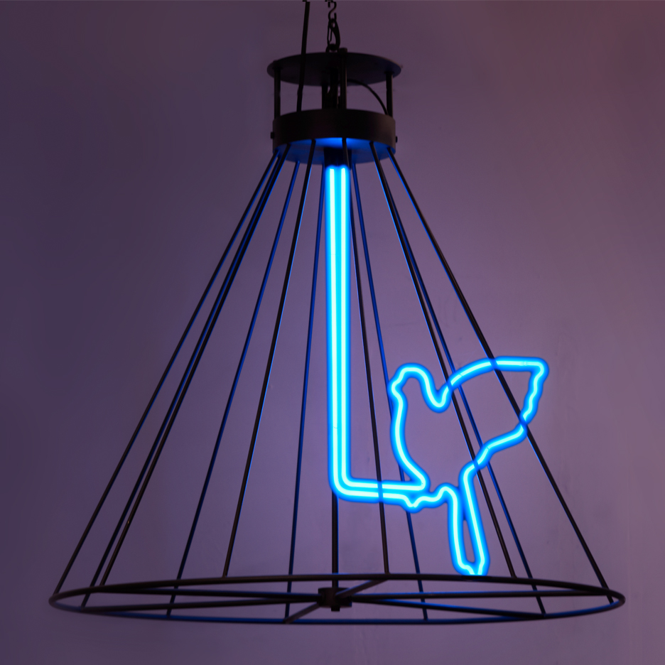 neon blue bird within a metal black hanging cage framework