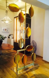 Aurora screen at Themes & Variations made of amber coloured resin supported by a solid brass frame